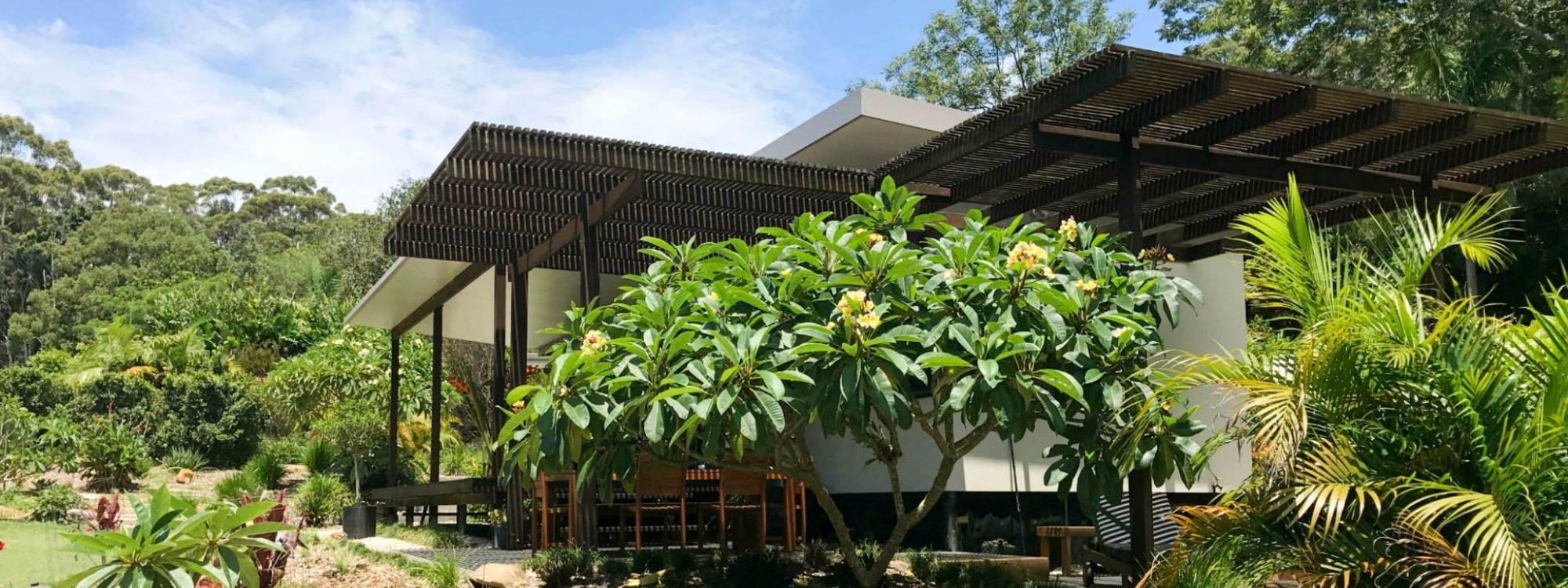 Outdoor dining, deck & BBQ area is shaded in summer by the magnificent frangipani tree.
