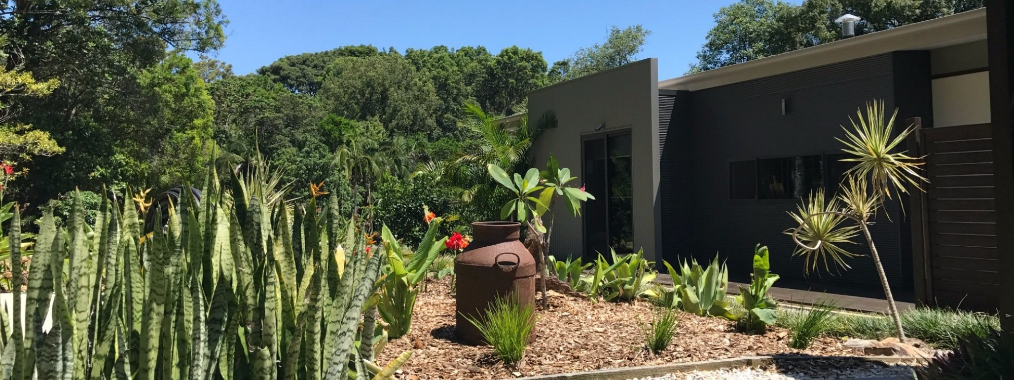 Tropical gardens with rustic farm equipment are located opposite the outdoor shower and laundry.